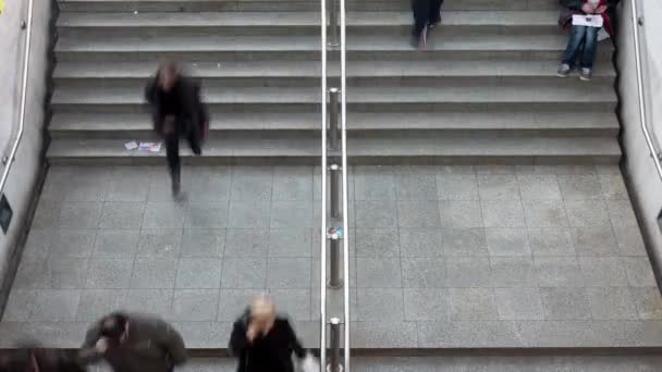 Time lapse of an overhead view of people walking towards and away from the entrance to the underground train station