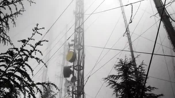 video of communication antennas and towers in a winter foggy day