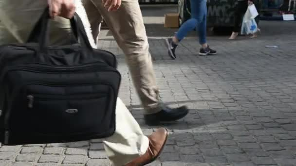 male with a business bag walking, stops and walk again on the pavement