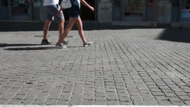 men and women's walking on the pavement on a sunny day