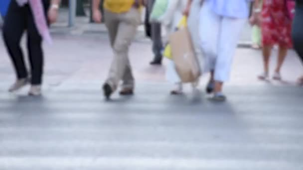 Blurry video of people crossing the street and some of them wearing protective mask for the covid 19 outbreak