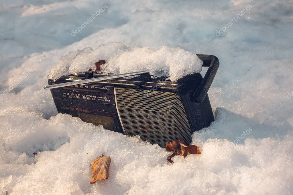 Old radio cassette player abandoned in the snow
