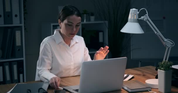 Businesswoman using laptop and writing notes at night office