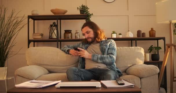 Mann schreibt SMS auf Handy zu Hause
