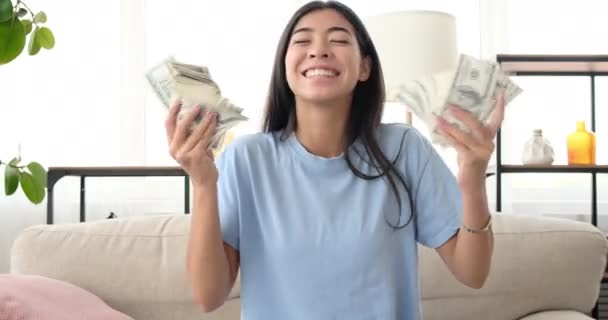 Excited woman shaking dollar bills in hand