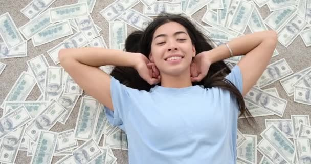 Woman lying down on scattered cash dollars