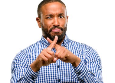African american man with beard annoyed with bad attitude making stop sign with hand, saying no, expressing security, defense or restriction, maybe pushing isolated over white background
