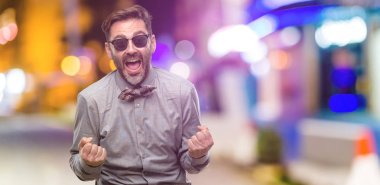Middle age man, with beard and bow tie happy and excited celebrating victory expressing big success, power, energy and positive emotions. Celebrates new job joyful at night club