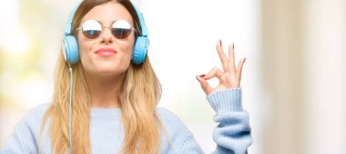 Young woman listen to music with headphone doing ok sign gesture with both hands expressing meditation and relaxation