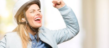 Young woman with bike helmet and earphones happy and excited celebrating victory expressing big success, power, energy and positive emotions. Celebrates new job joyful