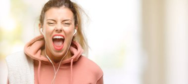 Young sport woman wearing workout sweatshirt stressful, terrified in panic, shouting exasperated and frustrated. Unpleasant gesture. Annoying work drives me crazy