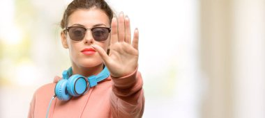 Young sport woman with headphones and sunglasses pointing away side with finger