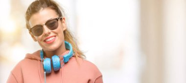 Young sport woman with headphones and sunglasses happy talking using a smartphone mobile phone