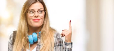 Young student woman with headphones and backpack raising finger, the number one