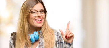 Young student woman with headphones and backpack pointing away side with finger