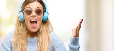 Young woman listen to music with headphone happy and surprised cheering expressing wow gesture