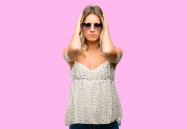 Young woman wearing sunglasses with heart shape covering ears ignoring annoying loud noise, plugs ears to avoid hearing sound. Noisy music is a problem.