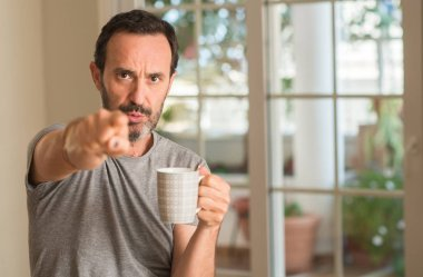 Middle age man drinking coffee in a cup pointing with finger to the camera and to you, hand sign, positive and confident gesture from the front