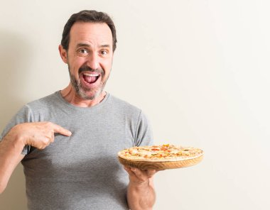 Senior man holding pizza with surprise face pointing finger to himself