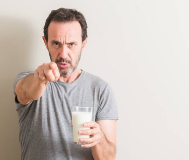 Senior man drinking a glass of milk pointing with finger to the camera and to you, hand sign, positive and confident gesture from the front