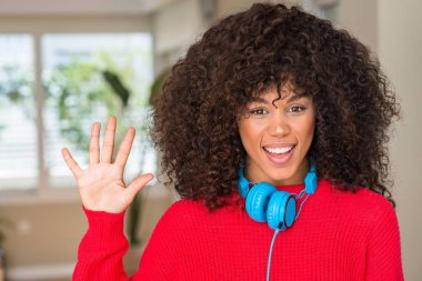 African american woman wearing headphones showing and pointing up with fingers number five while smiling confident and happy.