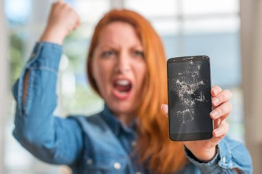 Redhead woman holding broken smartphone annoyed and frustrated shouting with anger, crazy and yelling with raised hand, anger concept