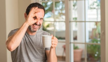 Middle age man drinking coffee in a cup with happy face smiling doing ok sign with hand on eye looking through fingers