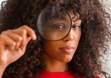 Curious african american woman looking through magnifying glass with a confident expression on smart face thinking serious