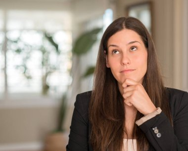 Young beautiful woman at home serious face thinking about question, very confused idea