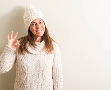 Middle age woman wearing wool winter cap doing ok sign with fingers, excellent symbol