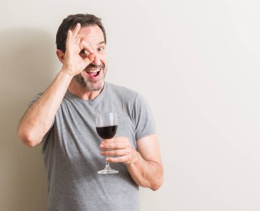 Senior man drinking red wine in a glass with happy face smiling doing ok sign with hand on eye looking through fingers