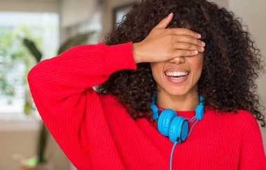 African american woman wearing headphones smiling and laughing with hand on face covering eyes for surprise. Blind concept.