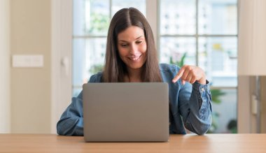 Young woman using laptop at home very happy pointing with hand and finger stock vector