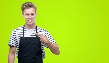 Young handsome blond man wearing apron with surprise face pointing finger to himself