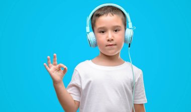 Dark haired little child listening music with headphones doing ok sign with fingers, excellent symbol