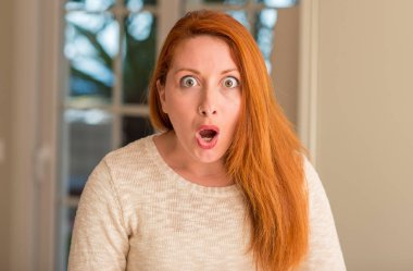 Redhead woman at home scared in shock with a surprise face, afraid and excited with fear expression