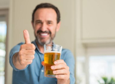 Middle age man drinking beer happy with big smile doing ok sign, thumb up with fingers, excellent sign