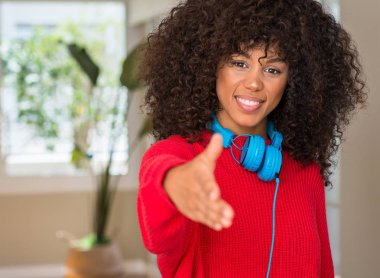 African american woman wearing headphones smiling friendly offering handshake as greeting and welcoming. Successful business.