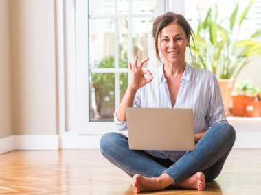 Middle aged woman using laptop at home doing ok sign with fingers, excellent symbol