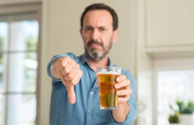 Middle age man drinking beer with angry face, negative sign showing dislike with thumbs down, rejection concept