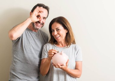 Middle age couple, woman and man, holding piggy bank with happy face smiling doing ok sign with hand on eye looking through fingers