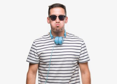 Handsome young man wearing headphones puffing cheeks with funny face. Mouth inflated with air, crazy expression.