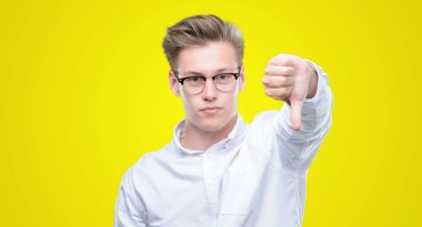 Young handsome blond man looking unhappy and angry showing rejection and negative with thumbs down gesture. Bad expression.