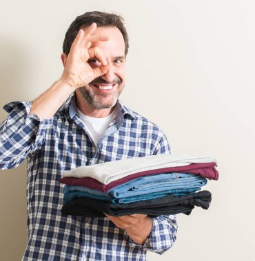 Senior man holding folded laundry clothes with happy face smiling doing ok sign with hand on eye looking through fingers