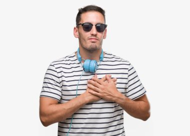 Handsome young man wearing headphones smiling with hands on chest with closed eyes and grateful gesture on face. Health concept.