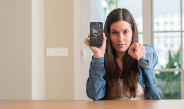 Brunette young woman holding broken smartphone pointing with finger to the camera and to you, hand sign, positive and confident gesture from the front