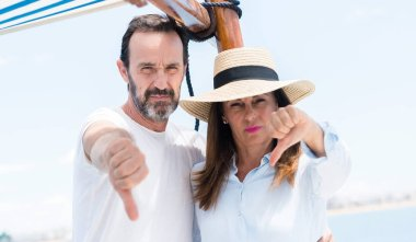 Middle age couple traveling on sailboat with angry face, negative sign showing dislike with thumbs down, rejection concept