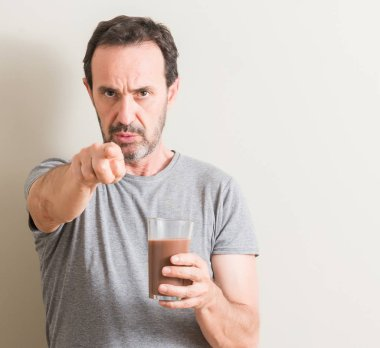 Senior man drinking chocolate milk shake pointing with finger to the camera and to you, hand sign, positive and confident gesture from the front