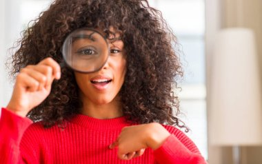 Curious african american woman looking through magnifying glass with surprise face pointing finger to himself