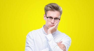 Young handsome blond man thinking looking tired and bored with depression problems with crossed arms.